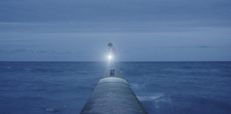 Person with a torch on a pier in front of a dark sea