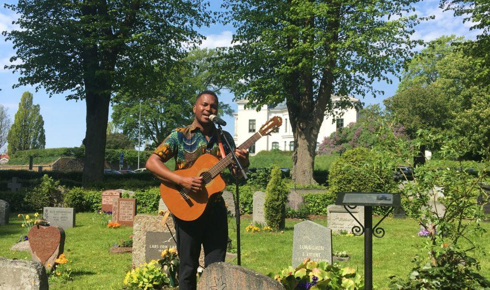 Gitarrist spelar på kyrkogård