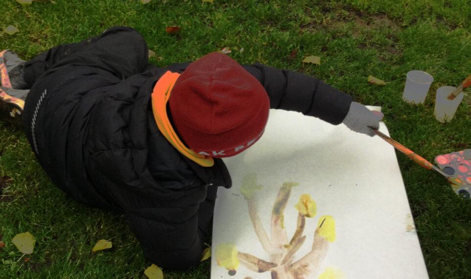 Ett barn målar av ett träd i parken