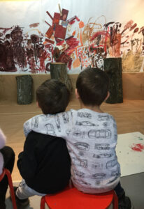 Två barn sitter med armen om varandra och tittar på ett konstverk