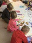 Barn sitter i en lång rad och målar