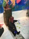 Ett barn sitter och målar på golvet