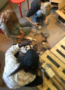 Barn skapar med trä och limpistoler