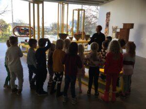 Barn får en visning av en utställning av en konstpedagog