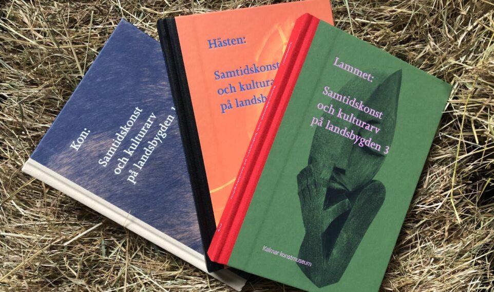 Tre böcker på en bakgrund av halm
