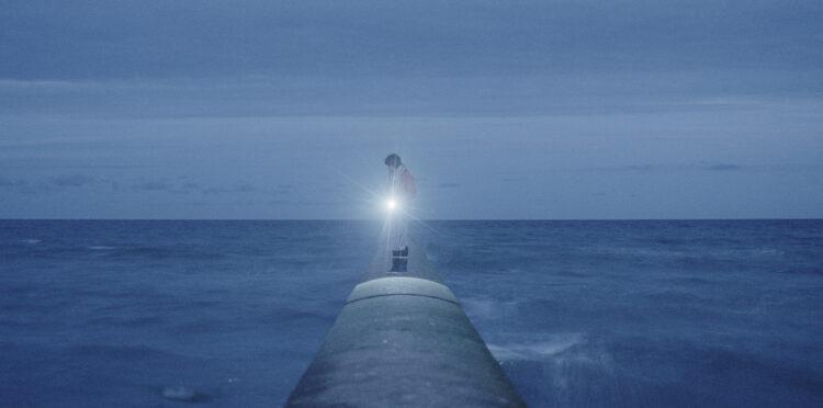 En person står på en pir med en ficklampa mot ett mörkt hav