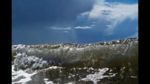 En våg rullar in mot en bakgrund av en solig himmel